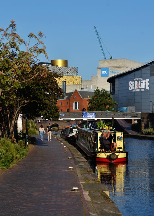 Walkers by a canal with the Library of Birmingham, the ICC and Sea Life Centre in the distance