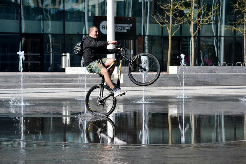 Cyclist doing wheelies in a shallow pool
