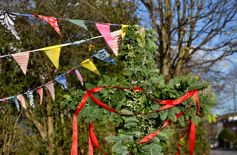 The wooden cross outside Christ Church decorated with foliage and bunting