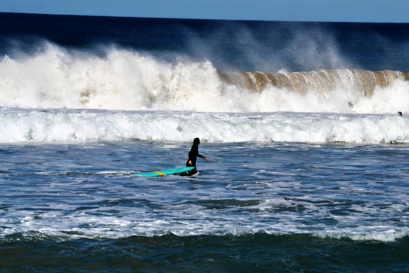 A surfer walking in the sea with a wave approaching