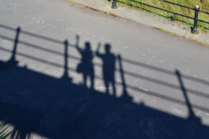 Shadows on the ground of people waving