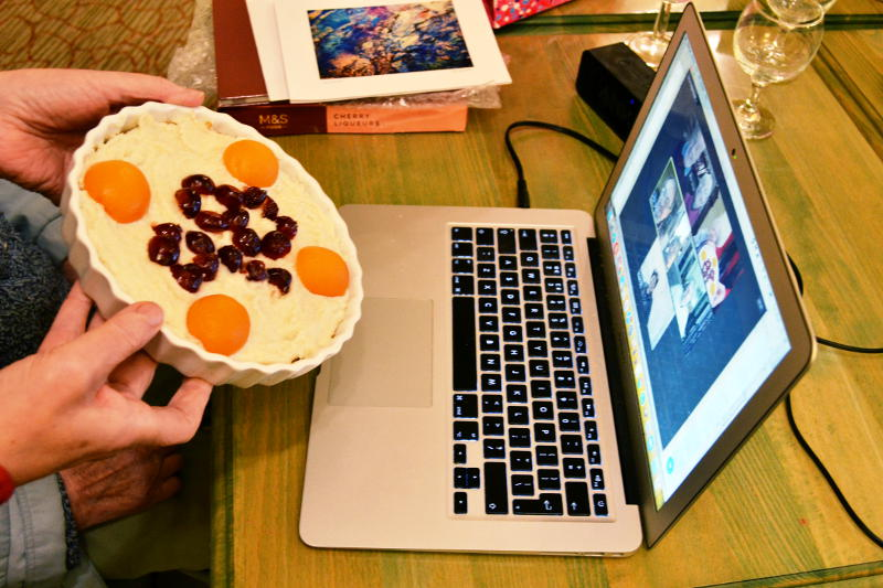 Holding up a cheesecake to a laptop running a Zoom session