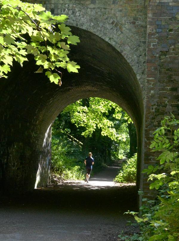 A runner going along a path under a bridge