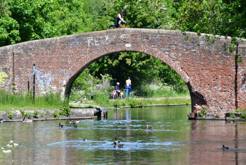 An old canal bridge, with walkers on and beside it