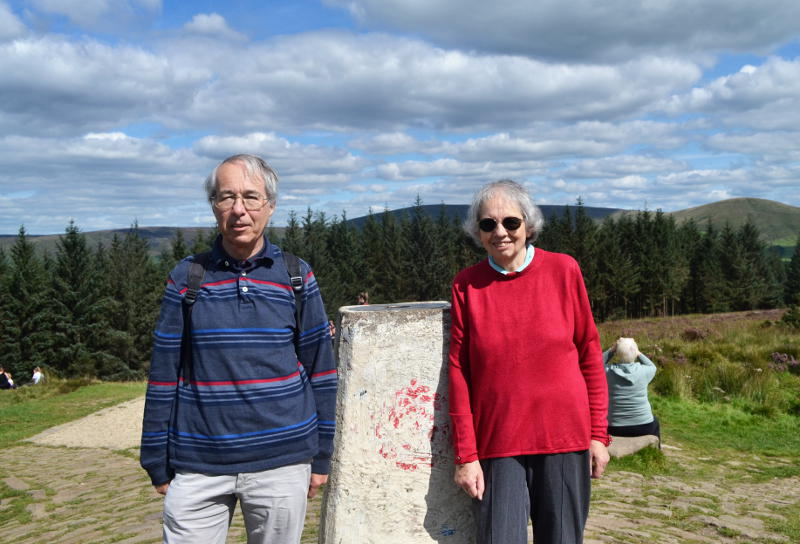 Phil and Miriam standing by an obelisk at the top of a hill