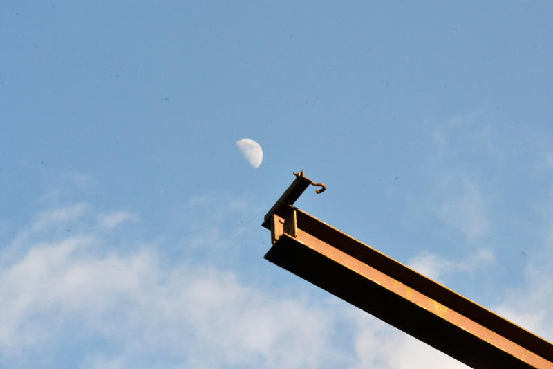 A nearly-full Moon by a metal beam