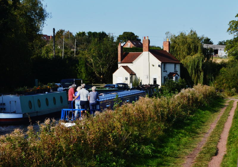 A canal boat passes a white cottage
