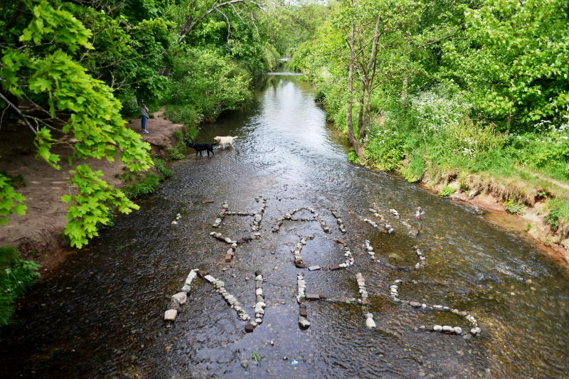 """""""Thank you NHS"""" written in stones in a river bed"""